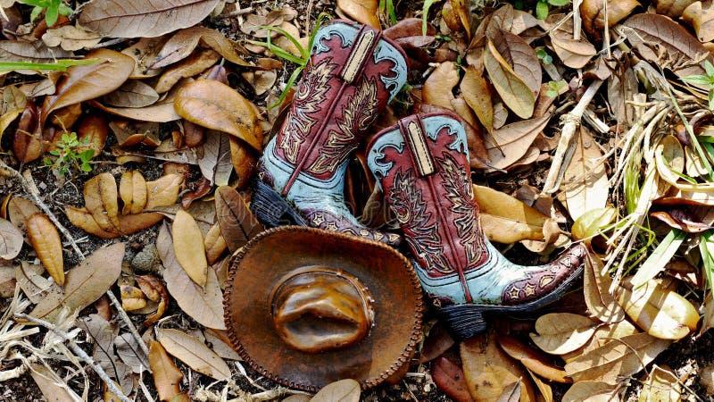 Cowboykängor och hatt som framlänges lägger i en säng av sidor royaltyfria bilder