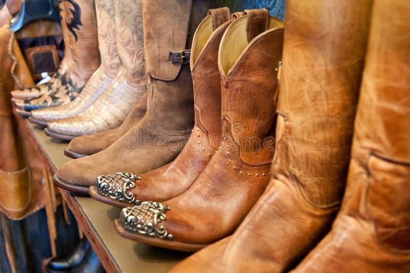 Cowboykängor på en hylla i ett lager arrangera i rak linje, closeupen royaltyfri foto
