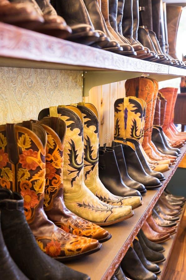 Cowboykängor på en hylla i ett lager som arrangera i rak linje arkivbild