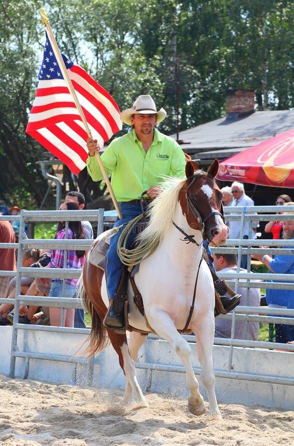 Cowboyridning med amerikanska flaggan. royaltyfria foton