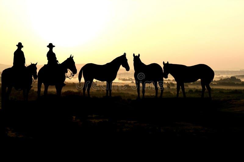 Cowboys et coucher du soleil photographie stock