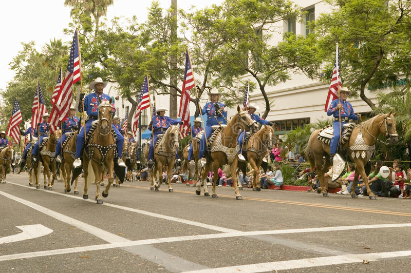 Cowboys on horseback with American Flags displayed during opening day parade down State Street, Santa Barbara, CA, Old Spanish Day. S Fiesta, August 2006 stock photo