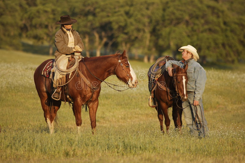 Cowboys Meeting In Meadow Stock Photo