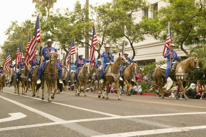 Cowboys op horseback met Amerikaanse die Vlaggen tijdens het openen dagparade worden getoond onderaan State Street, Santa Barbara stock foto