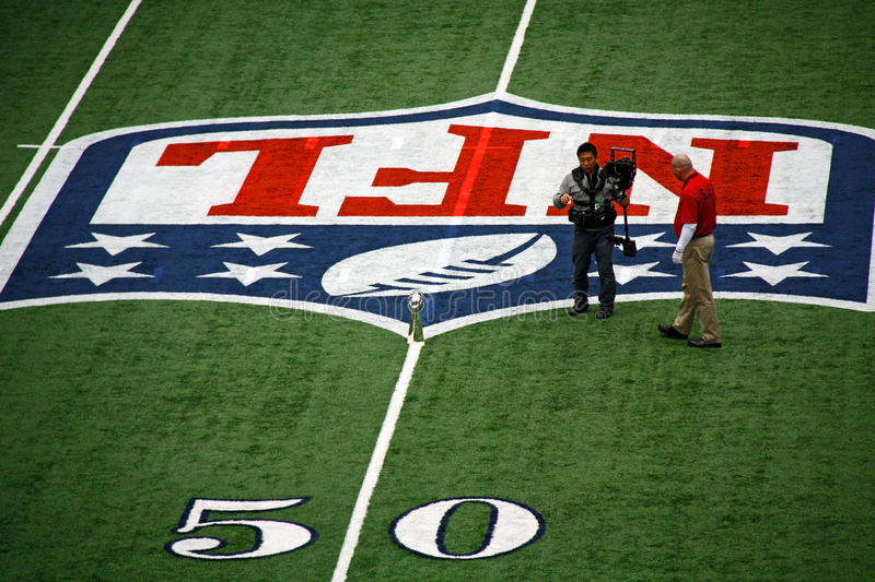 Cowboys Stadium 50 Yard Line Trophy. ARLINGTON - JAN 26: In preparation for the Packers Steelers Super Bowl XLV an unidentified cameraman and worker discuss stock photography