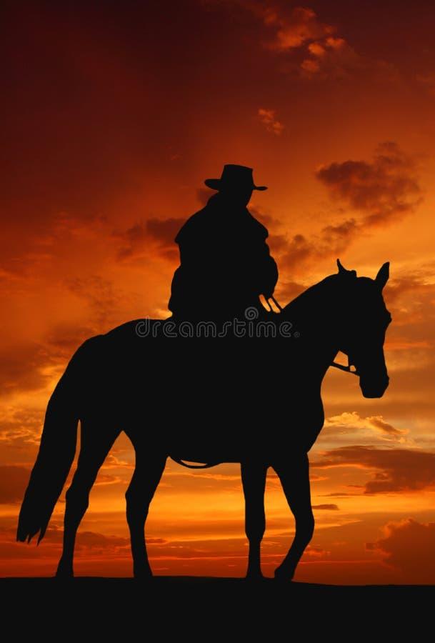 Cowboyschattenbild Im Sonnenaufgang Stockbild