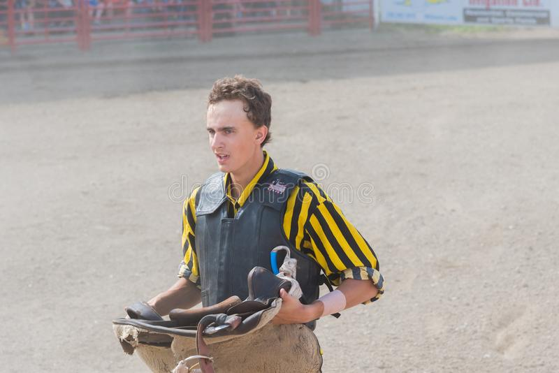 Cowboystände lasen mit Sattel am wilden Pferderennen lizenzfreie stockbilder