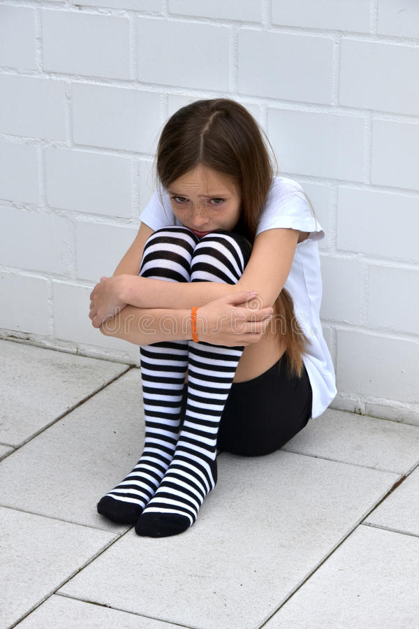 Cowering girl. Sad pubescent teenager girl cowering on the floor royalty free stock photography