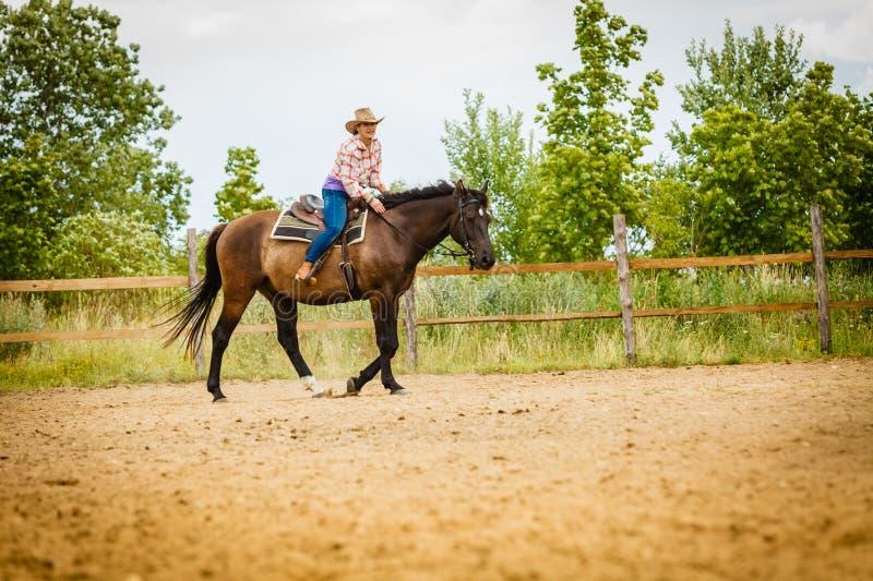 Cowgirl που κάνει την ιππασία στο λιβάδι επαρχίας στοκ φωτογραφία