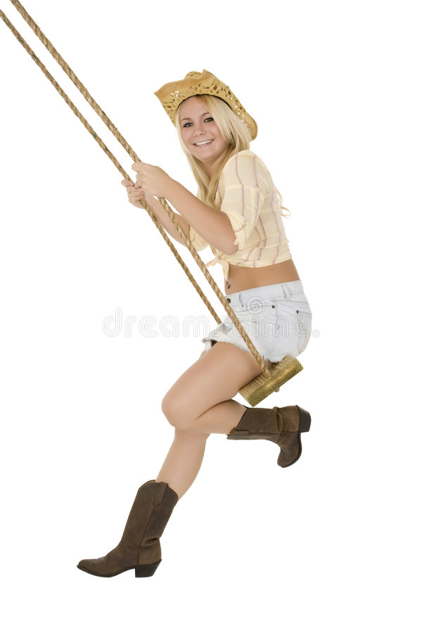 Beautiful Caucasian blond cowgirl playing on a wooden swing stock images