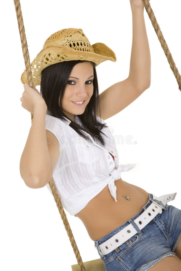 and beautiful Caucasian cowgirl playing on a wooden swing stock images