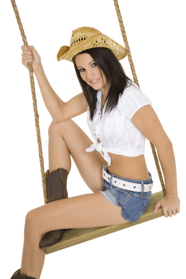 and beautiful Caucasian cowgirl playing on a wooden swing royalty free stock photos