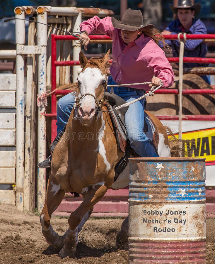 Cowgirl Barrel Racer. A cowgirl clears a barrel during a barrel racing event. The rodeo in Cottonwood, California is a popular event on Mother's Day weekend in royalty free stock photo