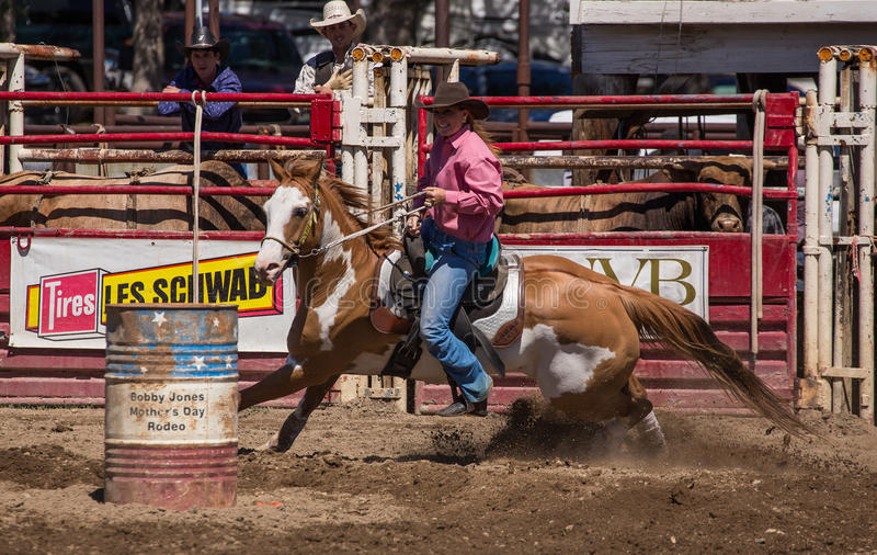 Cowgirl Barrel Racer. A cowgirl clears a barrel during a barrel racing event. The rodeo in Cottonwood, California is a popular event on Mother's Day weekend in royalty free stock photos