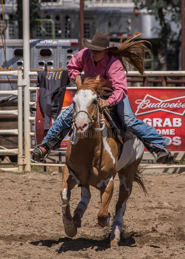 Cowgirl Barrel Racer. A cowgirl clears a barrel during a barrel racing event. The rodeo in Cottonwood, California is a popular event on Mother's Day weekend in stock images