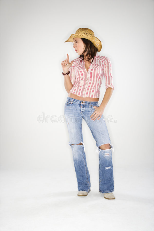 Cowgirl blowing imaginary gun. Young adult Caucasian woman wearing cowboy hat pointing finger upwards like gun and blowing away imaginary smoke royalty free stock photography