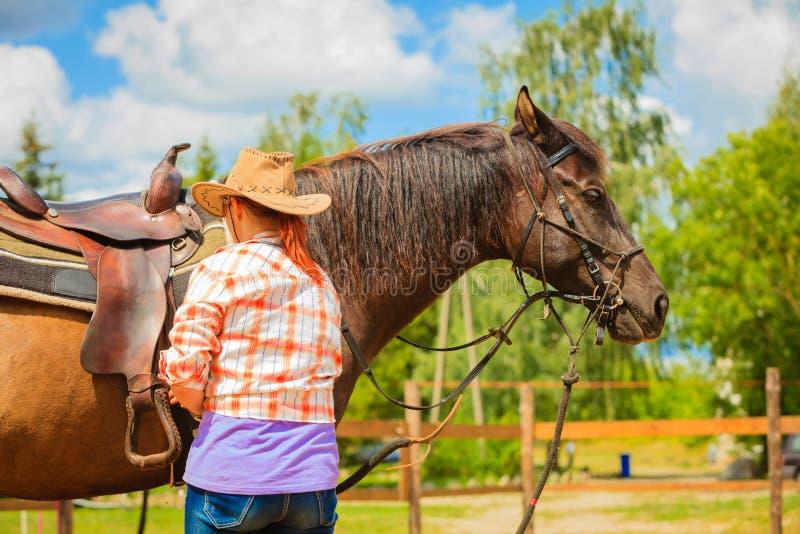 Cowgirl che ottiene cavallo pronto per il giro sulla campagna immagini stock
