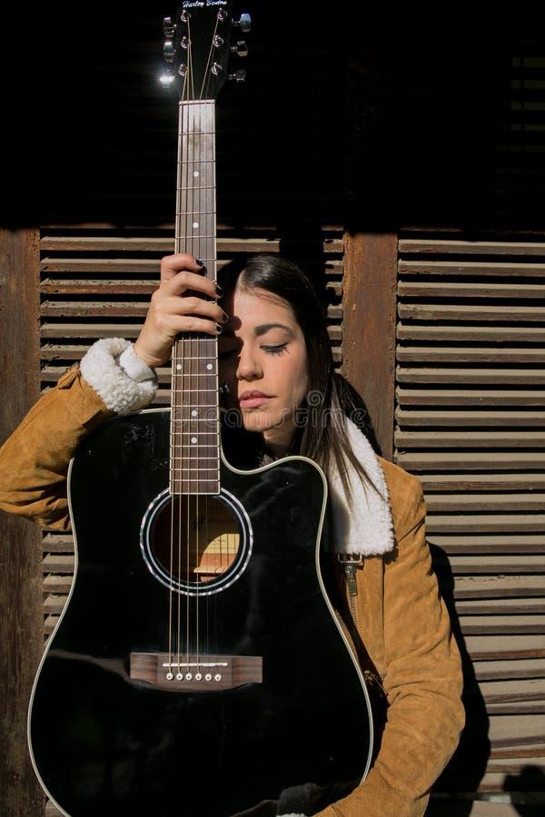 Cowgirl che posa con la chitarra fotografie stock