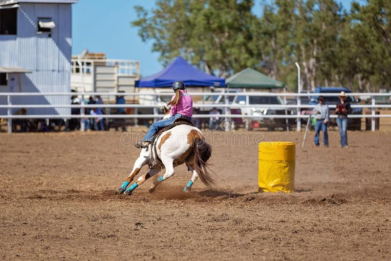Cowgirl Competing In Barrel Racing Competition At A Rodeo. A cowgirl competing in a barrel racing competition at a country rodeo royalty free stock photo