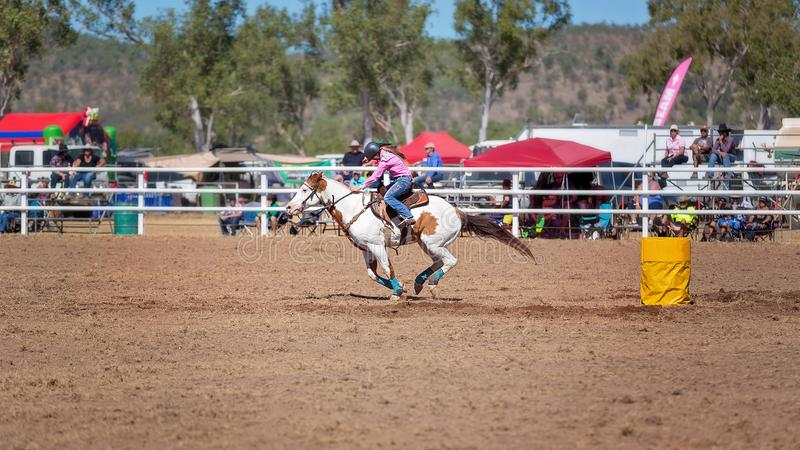 Cowgirl Barrel Racing At A Country Rodeo. Cowgirl competing in a barrel racing event at an Australian country rodeo stock photo