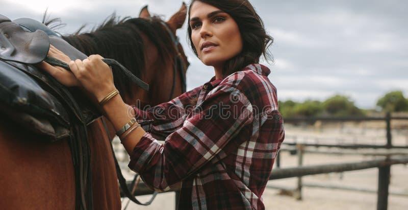 Cowgirl, das ein braunes Pferd sattelt lizenzfreie stockfotos