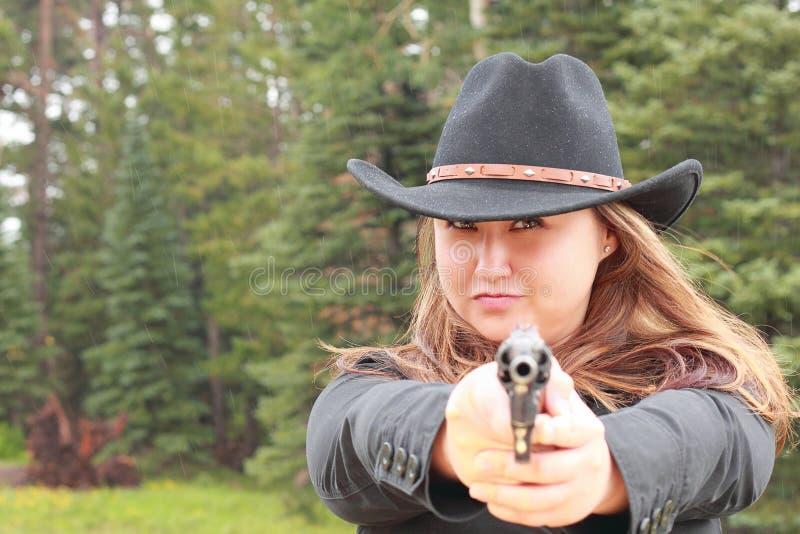 Cowgirl en revólver negro del Shooting de la muchacha en lluvia imagen de archivo
