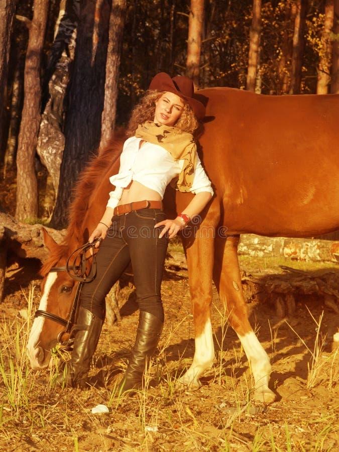 Cowgirl joven con su caballo rojo en la puesta del sol. imágenes de archivo libres de regalías