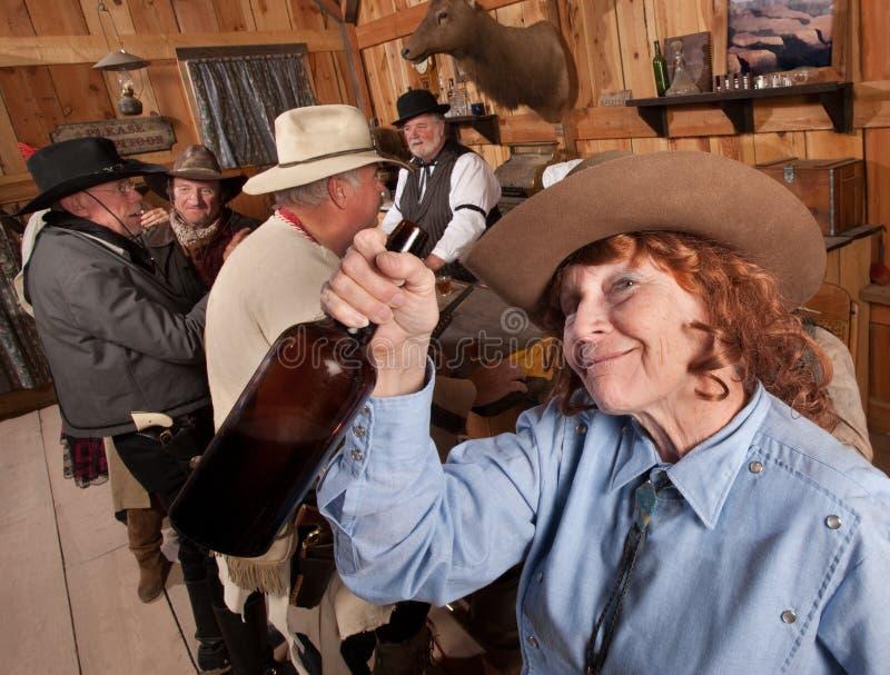 Cowgirl maggiore felice con la bottiglia immagine stock