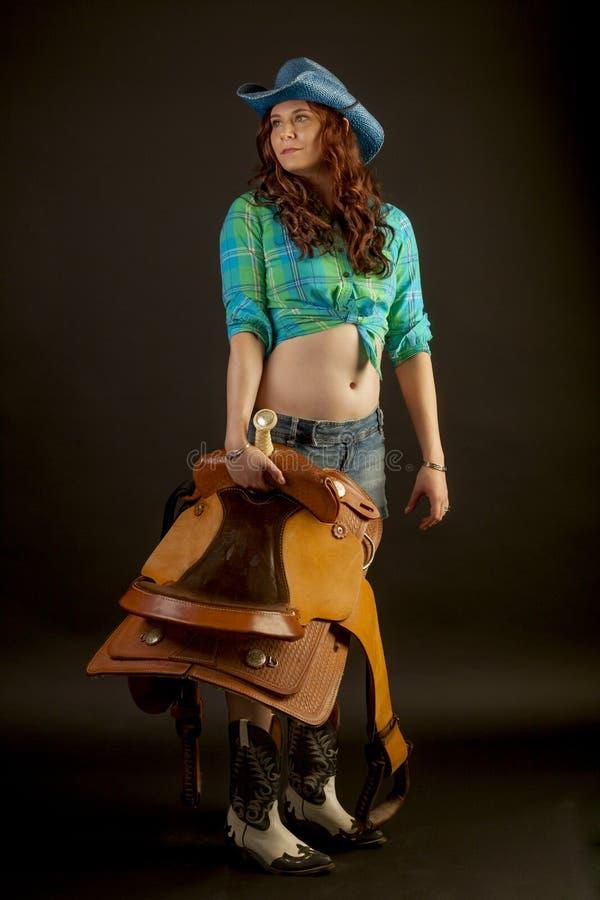 Cowgirl med en sadel arkivfoto