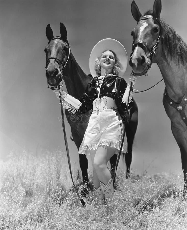 Cowgirl med två hästar royaltyfri bild