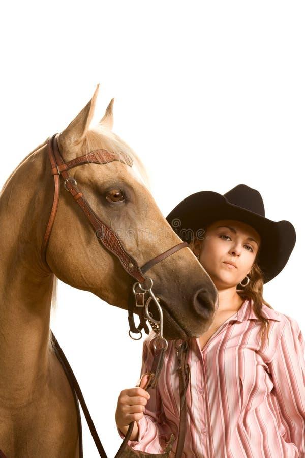 Cowgirl na terra arrendada do chapéu seu cavalo pelo breio foto de stock royalty free