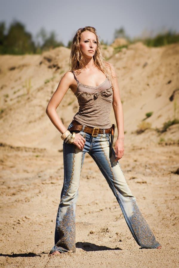 Download Cowgirl Nas Calças De Brim Em Um Fundo Arenoso Imagem de Stock - Imagem de posing, americano: 26507997