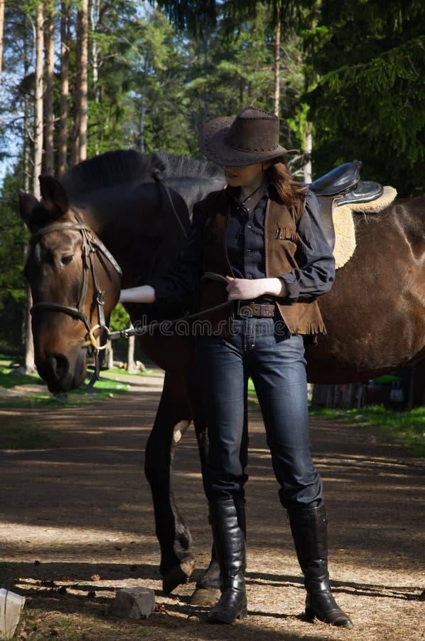 Cowgirl no chapéu que abraça seu cavalo foto de stock
