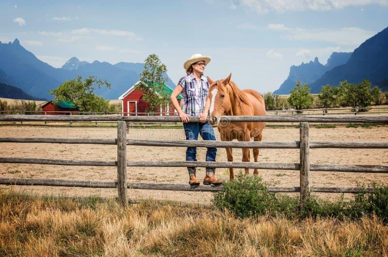 Cowgirl och hennes hästanseende vid ett trästaket fotografering för bildbyråer