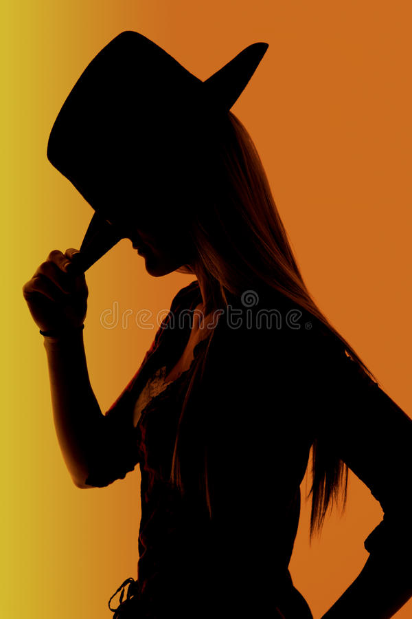 Cowgirl with orange background silhouette with highlights. Silhouette of cowgirl adjusting hat orange highlights royalty free stock photos