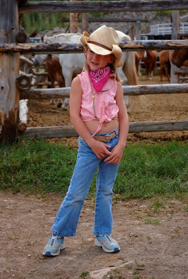 Cowgirl pequeno com fundo da cerca do cavalo imagem de stock royalty free