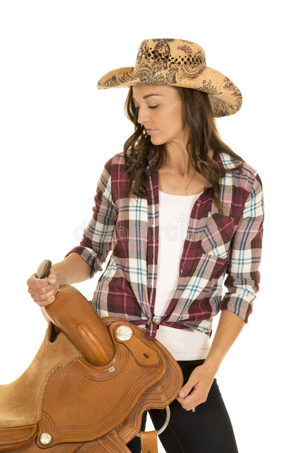 Cowgirl plaid shirt hat hold saddle on hip look down royalty free stock image
