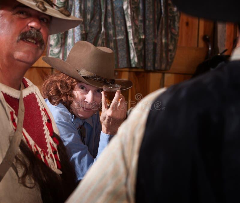 Cowgirl que brinda com uma bebida fotografia de stock