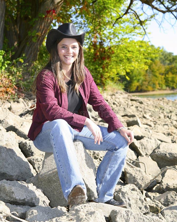 Cowgirl que senta-se em rochas foto de stock royalty free