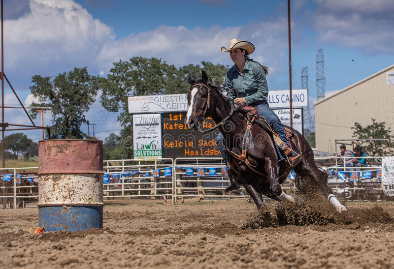 Cowgirl on the Ride. A cowgirl clears a barrel during a barrel racing event. The rodeo in Cottonwood, California is a popular event on Mother's Day weekend in stock photo