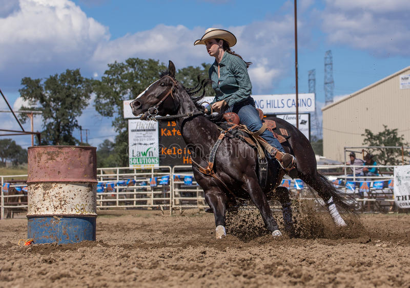 Cowgirl on the Ride. A cowgirl clears a barrel during a barrel racing event. The rodeo in Cottonwood, California is a popular event on Mother's Day weekend in royalty free stock photography