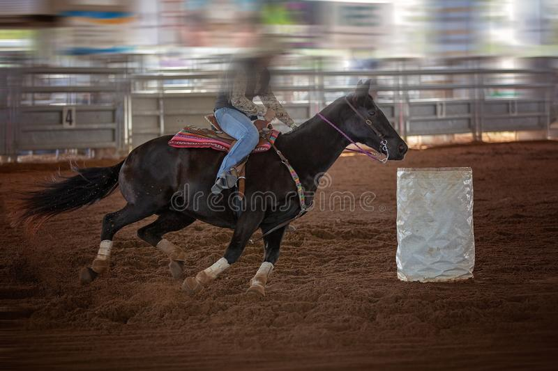Cowgirl Rides Horse At Speed In Rodeo Barrel Racing Competition. A cowgirl rides her horse at speed in a barrel racing competition at an indoor country rodeo royalty free stock photography