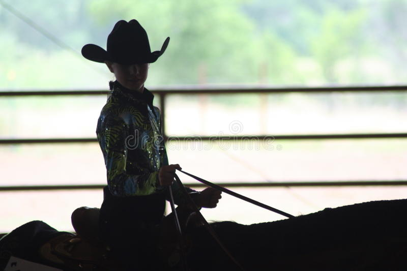 Silhouette of cowgirl in horse show royalty free stock image