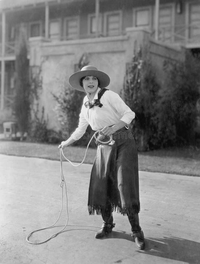 Cowgirl som använder lasson (alla visade personer inte är längre uppehälle, och inget gods finns Leverantörgarantier att det inte royaltyfria foton