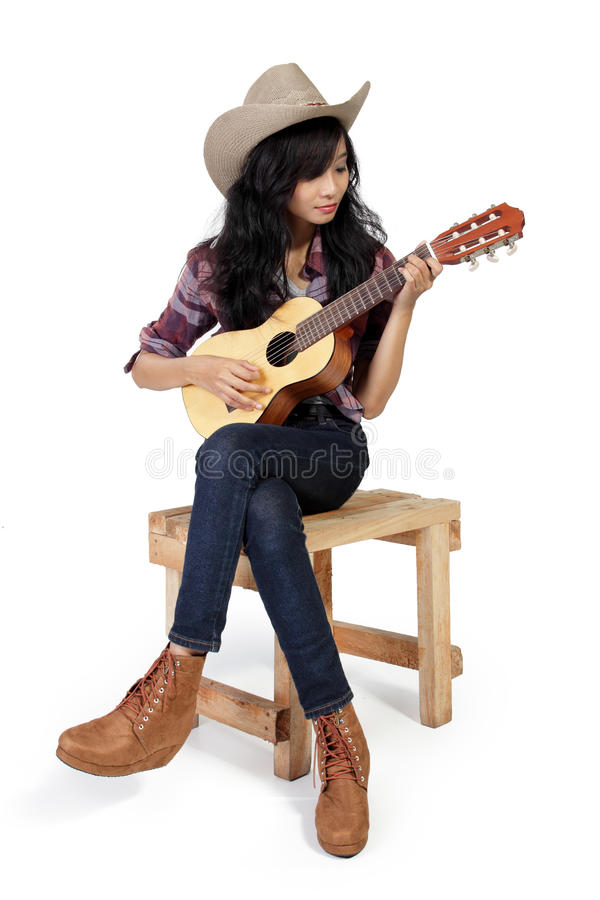 Cowgirl spielt Ukulele auf einem Stuhl lizenzfreies stockbild