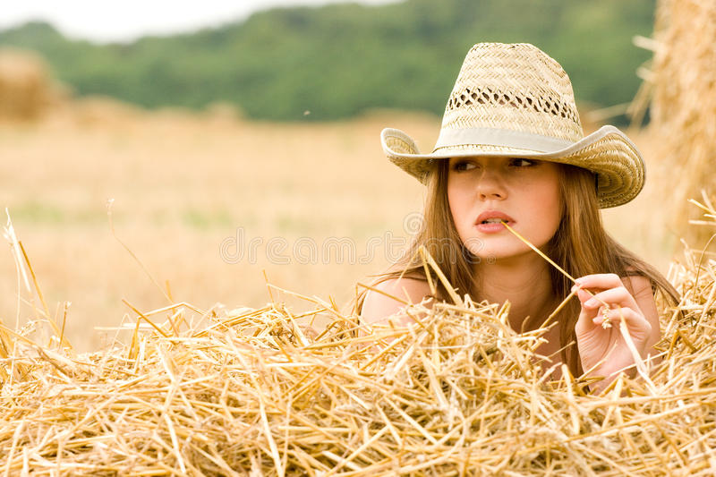 Cowgirl in straw. Beauty cowgirl relaxing in the straw in field stock photography