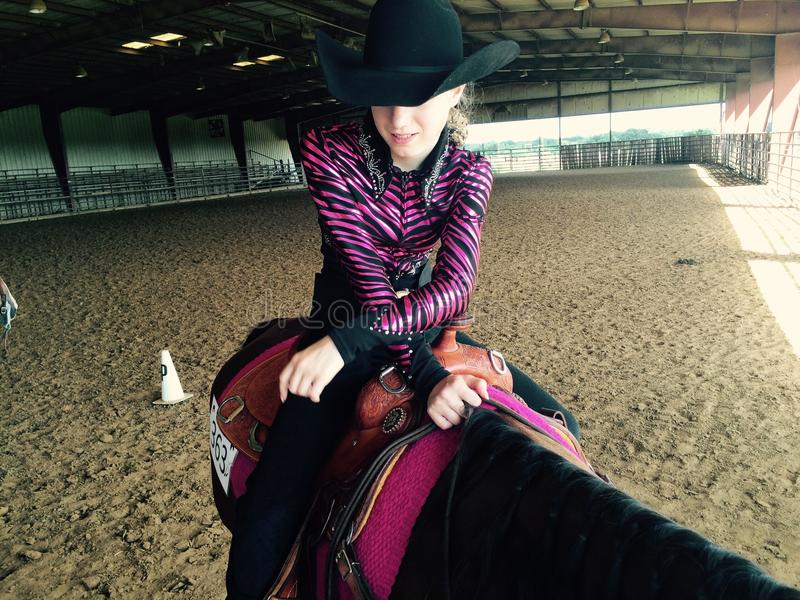 Girl in cowboy hat on horse in paddock royalty free stock photography