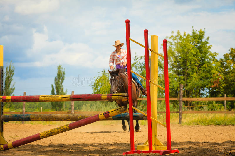 Cowgirl in western hat doing horse jumping stock images
