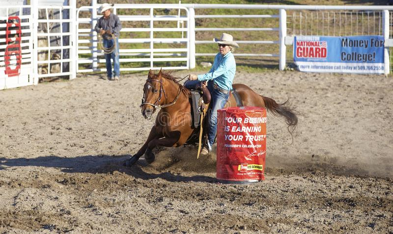 Cowgirls competing in barrel riding royalty free stock photography