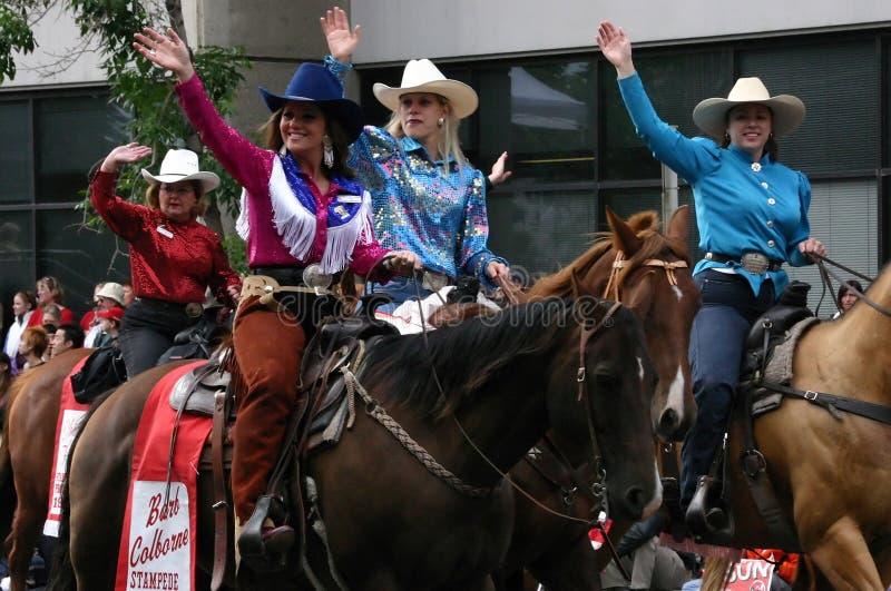 Cowgirls som rider hästar ståtar in arkivbild